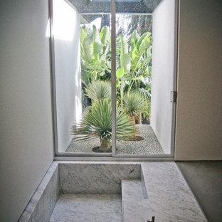 Ispirazione per una grande stanza da bagno padronale minimalista con vasca ad angolo, pareti grigie, pavimento in marmo, ante lisce, ante grigie, doccia a filo pavimento, WC sospeso, lavabo integrato, top in marmo, pavimento grigio e porta doccia a battente
