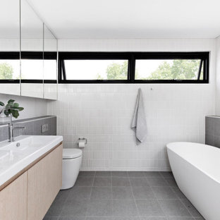 Design ideas for a mid-sized contemporary master bathroom in Sydney with light wood cabinets, a freestanding tub, white tile, gray tile, ceramic tile, white walls, porcelain floors, grey floor, a double vanity, a floating vanity, flat-panel cabinets, a console sink and white benchtops.