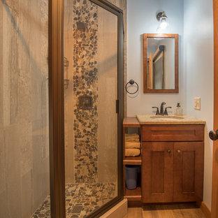 Foto de cuarto de baño con ducha, de estilo americano, de tamaño medio, con armarios estilo shaker, puertas de armario de madera en tonos medios, ducha esquinera, baldosas y/o azulejos beige, suelo de baldosas tipo guijarro, paredes azules, suelo de madera en tonos medios, lavabo bajoencimera, encimera de granito, suelo marrón, ducha con puerta con bisagras y encimeras marrones