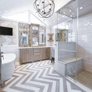 ヒューストンの中サイズのトランジショナルスタイルのおしゃれなマスターバスルーム (グレーのキャビネット、置き型浴槽、段差なし、グレーの壁、家具調キャビネット、珪岩の洗面台、グレーのタイル、磁器タイル、磁器タイルの床、アンダーカウンター洗面器) の写真