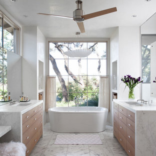 Inspiration for a mediterranean ensuite bathroom in Austin with flat-panel cabinets, medium wood cabinets, a freestanding bath and white walls.