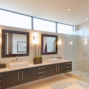 Large minimalist master porcelain tile and beige floor alcove shower photo in Dallas with flat-panel cabinets, dark wood cabinets, beige walls, a drop-in sink and a hinged shower door