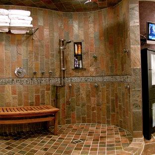 Modelo de cuarto de baño principal, contemporáneo, de tamaño medio, con lavabo sobreencimera, armarios tipo vitrina, puertas de armario negras, encimera de cemento, sanitario de una pieza, baldosas y/o azulejos multicolor, baldosas y/o azulejos de piedra, paredes púrpuras y suelo de pizarra