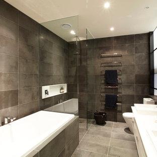 Пример оригинального дизайна: ванная комната в стиле лофт с накладной раковиной, белыми фасадами, накладной ванной, угловым душем, серой плиткой и белой столешницей