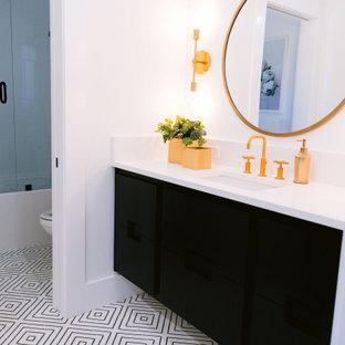 Modelo de cuarto de baño infantil, rural, de tamaño medio, con armarios con paneles lisos, puertas de armario negras, combinación de ducha y bañera, paredes blancas, suelo de azulejos de cemento, lavabo bajoencimera, encimera de cuarzo compacto, ducha con puerta con bisagras y encimeras blancas