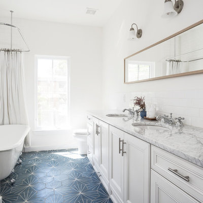 Example of a mid-sized farmhouse kids' white tile and subway tile blue floor claw-foot bathtub design in Austin with white cabinets, a two-piece toilet, white walls, an undermount sink, marble countertops, a hinged shower door, beaded inset cabinets and gray countertops