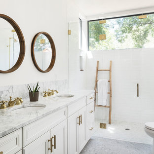 Example of a mid-sized country master white tile and subway tile mosaic tile floor and gray floor walk-in shower design in Austin with white cabinets, a two-piece toilet, white walls, an undermount sink, marble countertops, a hinged shower door, beaded inset cabinets and gray countertops