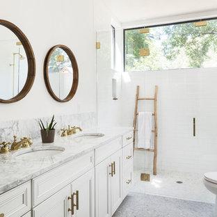 Bild på ett mellanstort lantligt grå grått en-suite badrum, med vita skåp, en kantlös dusch, en toalettstol med separat cisternkåpa, vit kakel, tunnelbanekakel, vita väggar, mosaikgolv, ett undermonterad handfat, marmorbänkskiva, grått golv, dusch med gångjärnsdörr och luckor med profilerade fronter