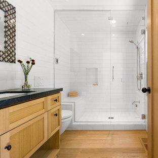 Foto på ett mellanstort retro badrum med dusch, med skåp i shakerstil, skåp i ljust trä, en dusch i en alkov, en vägghängd toalettstol, vit kakel, keramikplattor, vita väggar, ljust trägolv, ett undermonterad handfat, bänkskiva i täljsten, gult golv och dusch med gångjärnsdörr