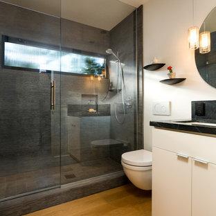 Foto de cuarto de baño con ducha, retro, pequeño, con armarios con paneles lisos, puertas de armario blancas, ducha empotrada, sanitario de pared, baldosas y/o azulejos grises, baldosas y/o azulejos de piedra, paredes blancas, suelo de madera clara, lavabo bajoencimera, encimera de esteatita, suelo amarillo y ducha con puerta con bisagras