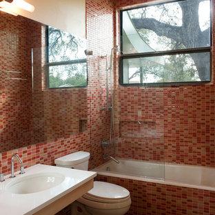 Ispirazione per una piccola stanza da bagno contemporanea con lavabo sottopiano, ante lisce, ante in legno chiaro, top in quarzo composito, vasca ad alcova, vasca/doccia, WC monopezzo, piastrelle rosa, piastrelle di vetro, pareti arancioni e pavimento in cemento