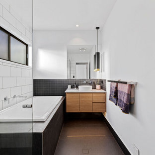 Inspiration for a contemporary bathroom in Sunshine Coast with flat-panel cabinets, medium wood cabinets, a drop-in tub, black and white tile, white walls, a vessel sink, grey floor and white benchtops.