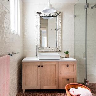 Стильный дизайн: ванная комната среднего размера в стиле шебби-шик с фасадами в стиле шейкер, светлыми деревянными фасадами, бежевыми стенами, душевой кабиной, настольной раковиной, двойным душем, белой плиткой, керамогранитной плиткой, полом из терракотовой плитки, столешницей из искусственного камня, красным полом и душем с распашными дверями - последний тренд