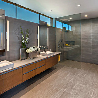 Large minimalist master gray tile and porcelain tile porcelain tile and gray floor bathroom photo in Phoenix with flat-panel cabinets, medium tone wood cabinets, a wall-mount toilet, gray walls, a vessel sink and white countertops