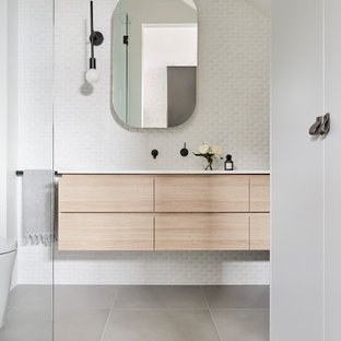 This is an example of a contemporary bathroom in Melbourne with flat-panel cabinets, light wood cabinets, white tile, mosaic tile, white walls, an undermount sink, grey floor, white benchtops, a single vanity, a floating vanity and vaulted.