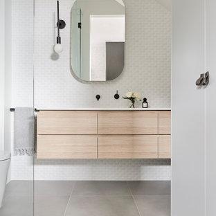 Bild på ett funkis vit vitt badrum, med släta luckor, skåp i ljust trä, vit kakel, mosaik, vita väggar, ett undermonterad handfat och grått golv