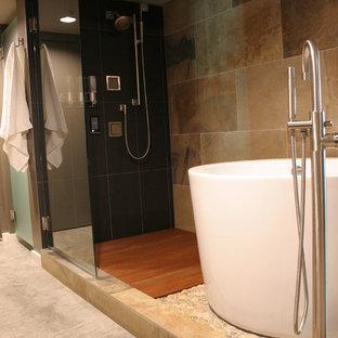 Inspiration pour une petit salle de bain principale traditionnelle avec un placard à porte plane, des portes de placard en bois brun, un bain japonais, une douche ouverte, un bidet, un carrelage noir, un carrelage de pierre, un mur gris, béton au sol, un lavabo intégré, un plan de toilette en quartz, un sol gris, une cabine de douche à porte battante et un plan de toilette gris.