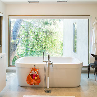 Large contemporary ensuite bathroom in Los Angeles with a freestanding bath, flat-panel cabinets, white cabinets, quartz worktops and beige floors.