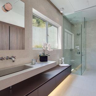 ロサンゼルスの広いモダンスタイルのおしゃれなバスルーム (浴槽なし) (開き戸のシャワー、フラットパネル扉のキャビネット、濃色木目調キャビネット、コーナー設置型シャワー、グレーのタイル、石タイル、グレーの壁、クッションフロア、横長型シンク、人工大理石カウンター) の写真