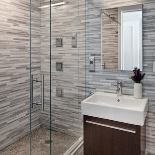 Example of a trendy master gray tile and matchstick tile ceramic floor alcove shower design in New York with a wall-mount sink, flat-panel cabinets, dark wood cabinets and multicolored walls