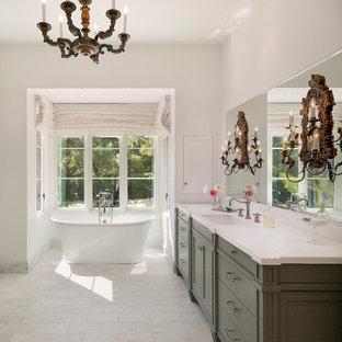 Esempio di un'ampia stanza da bagno padronale mediterranea con ante con riquadro incassato, ante verdi, vasca freestanding, pareti bianche, pavimento in gres porcellanato e lavabo sottopiano