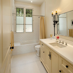 Mid-sized tuscan white tile ceramic floor bathroom photo in Santa Barbara with recessed-panel cabinets, yellow cabinets, a one-piece toilet, beige walls and an undermount sink