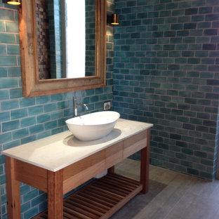 Ejemplo de cuarto de baño costero con lavabo sobreencimera, armarios tipo mueble, puertas de armario de madera oscura, encimera de piedra caliza, baldosas y/o azulejos azules, baldosas y/o azulejos de porcelana, paredes azules y suelo de baldosas de porcelana