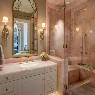 Modelo de cuarto de baño principal, tradicional renovado, con armarios con paneles con relieve, puertas de armario blancas, ducha empotrada, baldosas y/o azulejos rosa, baldosas y/o azulejos de mármol, paredes beige, suelo de mármol, lavabo bajoencimera, encimera de ónix, suelo rosa, ducha con puerta con bisagras y encimeras rosas