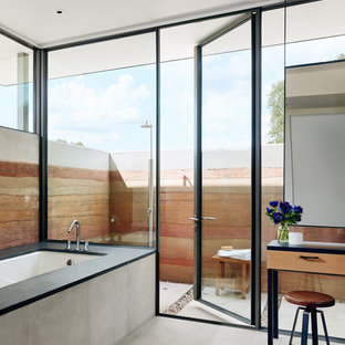 Inspiration for a southwestern master gray floor bathroom remodel in Other with an undermount tub