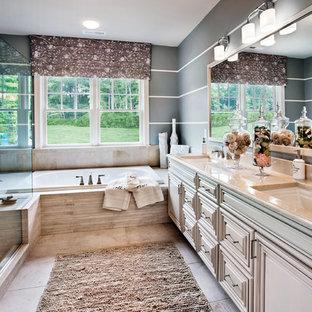 Diseño de cuarto de baño tradicional renovado con lavabo bajoencimera, armarios con paneles con relieve, puertas de armario beige, bañera encastrada, ducha esquinera y baldosas y/o azulejos beige
