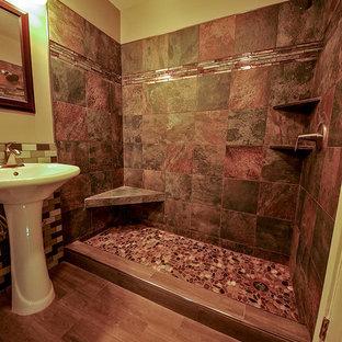 Diseño de cuarto de baño principal, rural, de tamaño medio, con lavabo con pedestal, ducha doble, sanitario de dos piezas, paredes beige y suelo de baldosas de porcelana