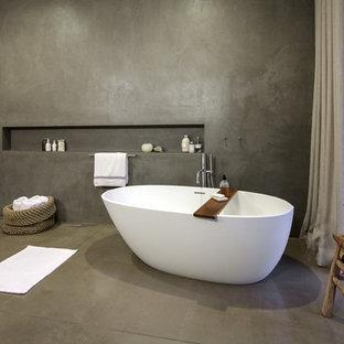Modelo de cuarto de baño principal, contemporáneo, grande, con lavabo suspendido, bañera exenta, ducha a ras de suelo, sanitario de pared, paredes grises y suelo de cemento