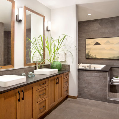 Inspiration for a rustic master gray tile gray floor drop-in bathtub remodel in Other with a vessel sink, recessed-panel cabinets and medium tone wood cabinets
