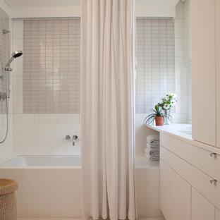 Ispirazione per una stanza da bagno minimal con lavabo sottopiano, ante lisce, ante bianche, vasca sottopiano, vasca/doccia e piastrelle grigie
