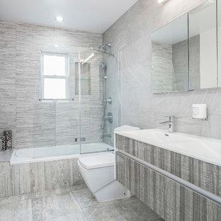 Imagen de cuarto de baño infantil, contemporáneo, grande, con puertas de armario grises, bañera encastrada, ducha empotrada, sanitario de una pieza, baldosas y/o azulejos grises, baldosas y/o azulejos de porcelana, paredes grises, suelo de baldosas de cerámica, lavabo encastrado, encimera de ónix, suelo gris, ducha con puerta con bisagras y encimeras blancas