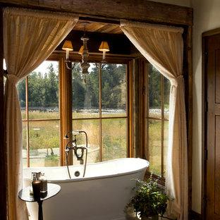 Foto de cuarto de baño principal, rústico, de tamaño medio, con bañera exenta, baldosas y/o azulejos beige, baldosas y/o azulejos de cerámica, paredes beige y suelo de baldosas de cerámica