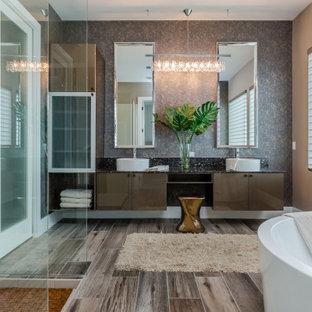 Inredning av ett modernt svart svart en-suite badrum, med släta luckor, bruna skåp, ett fristående badkar, en öppen dusch, beige kakel, bruna väggar, ett fristående handfat, brunt golv och med dusch som är öppen