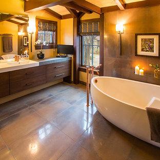 カルガリーの中サイズのエクレクティックスタイルのおしゃれなマスターバスルーム (フラットパネル扉のキャビネット、濃色木目調キャビネット、置き型浴槽、ダブルシャワー、壁掛け式トイレ、磁器タイル、黄色い壁、磁器タイルの床、茶色いタイル) の写真