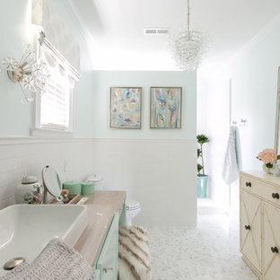 Пример оригинального дизайна: ванная комната в стиле шебби-шик с бирюзовыми фасадами, белыми стенами, полом из мозаичной плитки, настольной раковиной, столешницей из дерева и белым полом