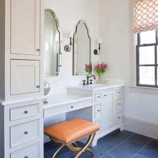 Modelo de cuarto de baño clásico con lavabo bajoencimera, armarios con paneles empotrados, puertas de armario beige, encimera de mármol, paredes blancas y suelo negro