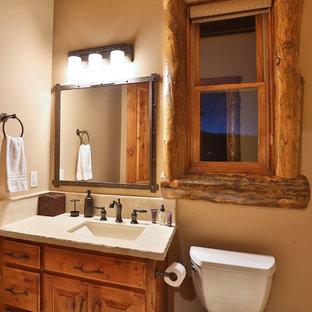 Rustik inredning av ett mellanstort badrum med dusch, med ett undermonterad handfat, luckor med upphöjd panel, skåp i mellenmörkt trä, bänkskiva i betong, en toalettstol med hel cisternkåpa och beige väggar