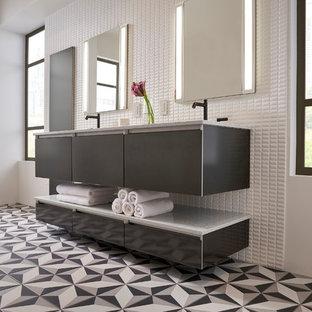 Esempio di una grande stanza da bagno padronale minimalista con ante di vetro, ante grigie, vasca freestanding, piastrelle bianche, piastrelle in ceramica, pareti bianche, pavimento con piastrelle in ceramica, lavabo sottopiano, top in quarzo composito e pavimento multicolore