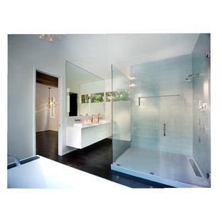 アトランタの大きいモダンスタイルのおしゃれなマスターバスルーム (フラットパネル扉のキャビネット、白いキャビネット、置き型浴槽、コーナー設置型シャワー、青いタイル、サブウェイタイル、白い壁、濃色無垢フローリング、ベッセル式洗面器、珪岩の洗面台) の写真
