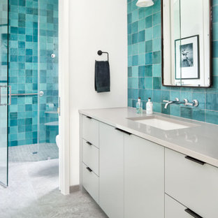 Example of a mid-sized trendy 3/4 blue tile and porcelain tile ceramic tile, gray floor, single-sink, shiplap ceiling and shiplap wall bathroom design in Austin with flat-panel cabinets, white cabinets, a two-piece toilet, white walls, an undermount sink, solid surface countertops, a hinged shower door, white countertops and a built-in vanity