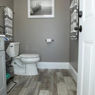 Idee per una piccola stanza da bagno con doccia design con consolle stile comò, ante grigie, pareti grigie, pavimento in laminato, top in superficie solida, pavimento grigio, top bianco e WC a due pezzi