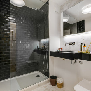 Design ideas for a medium sized contemporary shower room bathroom in London with open cabinets, black cabinets, an alcove shower, a wall mounted toilet, black tiles, metro tiles, white walls, an integrated sink, beige floors and black worktops.
