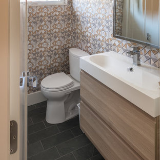 Example of a small trendy 3/4 slate floor and black floor bathroom design in Detroit with flat-panel cabinets, light wood cabinets, a one-piece toilet, beige walls, a trough sink and quartzite countertops
