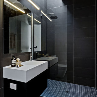 Inspiration for a contemporary 3/4 bathroom in Perth with flat-panel cabinets, black cabinets, an open shower, black tile, black walls, an integrated sink, black floor, an open shower and white benchtops.