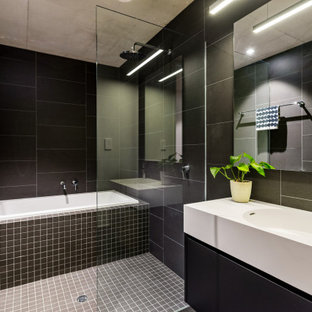 Mid-sized contemporary master wet room bathroom in Perth with flat-panel cabinets, black cabinets, a drop-in tub, black tile, porcelain tile, an integrated sink, grey floor and white benchtops.