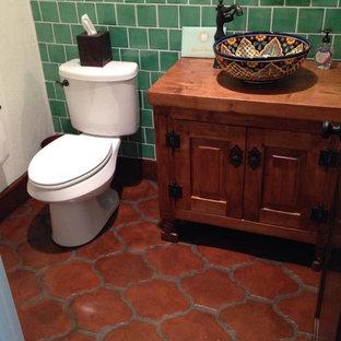 Diseño de cuarto de baño con ducha, mediterráneo, de tamaño medio, con armarios tipo mueble, puertas de armario de madera en tonos medios, sanitario de dos piezas, baldosas y/o azulejos verdes, baldosas y/o azulejos de cerámica, paredes blancas, suelo de baldosas de terracota, lavabo sobreencimera, encimera de cobre, suelo naranja y encimeras marrones